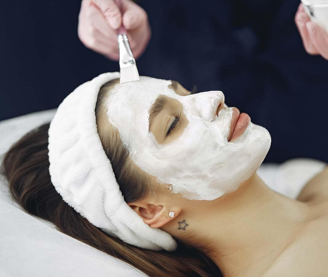 Woman receiving facial peel at spa