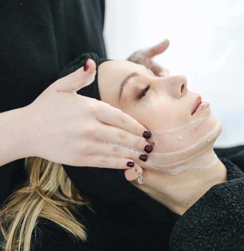 Woman getting skincare cleanser at day spa